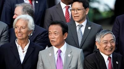 Japan's Finance Minister Taro Aso stands next to IMF Managing Director Christine Lagarde
