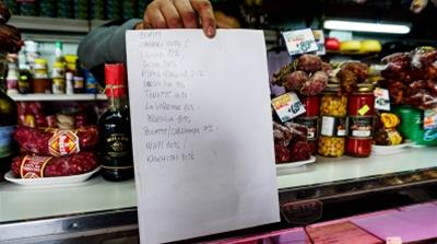 Luislist: Luis Coronel holds out a list of products offered at the cheese and charcuterie shop where he works whose prices from venders are slated to rise/Photo: Natalie Alcoba