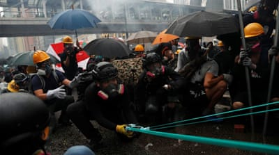 Hong Kong police draw guns, use water cannon in clashes