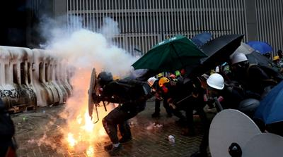 Demonstrators take cover during a protest in Hong Kong, China [Danish Siddiqui/Reuters]
