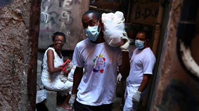 A volunteer carries donated aid for poor families at the Rocinha slum as the coronavirus disease (COVID-19) outbreak continues in Rio de Janeiro, Brazil March 27, 2020. [REUTERS/Pilar Olivares]