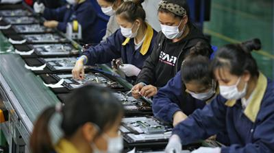 Employees, wearing masks, work on a production line manufacturing display monitors at a TPV factory in Wuhan, Hubei province, the epicentre of the novel coronavirus disease (COVID-19) outbreak in Chin