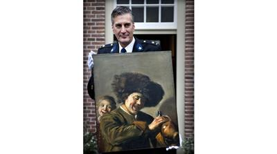 This photograph taken on November 3, 2011, shows District Chief of Alblasserwaard, Bart Willemsen showing the recovered painting