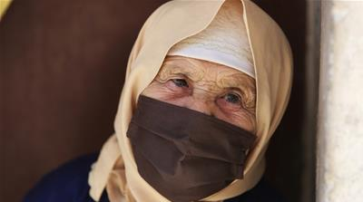 A Palestinian refugee woman wearing a face mask sits inside the Wavel refugee camp in Baalbek, Lebanon, April 29, 2020 [Aziz Taher/Reuters/Daylife]