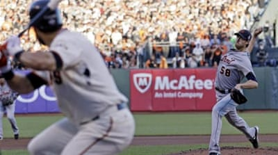 A trainer checks Fister after he is hit by ball off the bat of San Francisco Giants' Gregor Blanco [AP]
