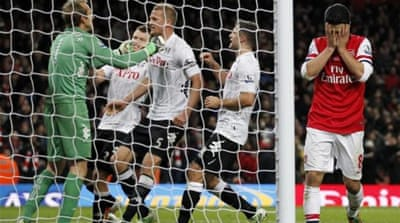 Fulham goalie Mark Schwarzer (L) celebrates with teammates as Arteta hides his head in shame [AFP]