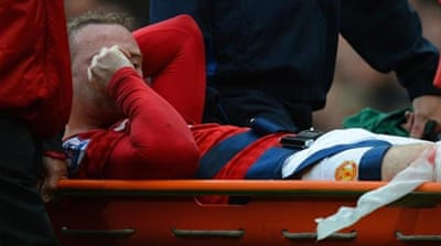 Ouch! Rooney had to be stretchered off after being caught by the boot of Fulham's Hugo Rodallega [EPA]