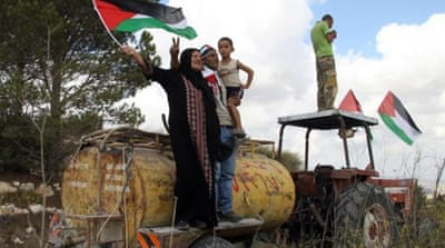 Palestinians remove Hebrew written by Israeli settlers on a water tank near Burka [AP]