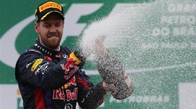 Familiar taste: Vettel gets another champagne shower in Brazil after winning his ninth race in a row [AFP]