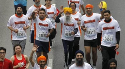 Marathon runner Fauja Singh (C) enjoys his last race alongside a group from the local Sikh community [Reuters]