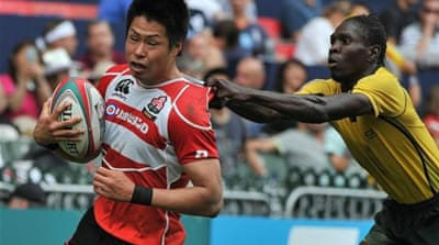 Jamaica's Andrew Hylton (R) tries to stop Japan's Kazushi Hano from scoring during Hong Kong Rugby Sevens [AFP]