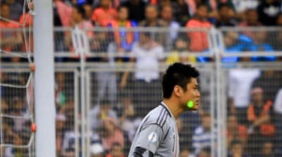 What appears to be a laser shining in the eyes of Japan's goalkeeper Eiji Kawashima during Jordan match [AP]