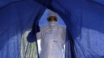 A Cuban nurse enters a tent during a practice drill at a training camp in Havana, Cuba [AP]