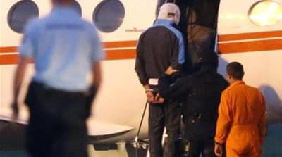 An alleged jihadist is escorted by French police onto an airplane bound for Paris [EPA]