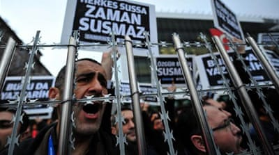 Staff members and supporters of Zaman newspaper shout slogans and hold placards reading 'Free press can not be silenced' during a protest against a raid by counter-terror police in Istanbul [AFP/Getty Images]