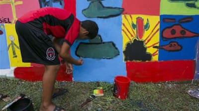 A youth paints in the walls of what used to be the Panamanian military headquarters, one day before the 25th anniversary of the US invasion, in what's now a park in El Chorrillo community of Panama City [AP]