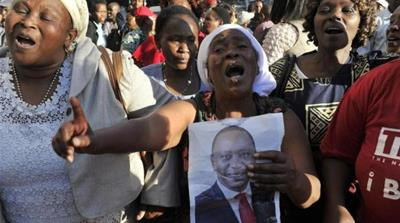 Supporters of Kenyatta celebrate following the ICC ruling to drop charges [AFP]