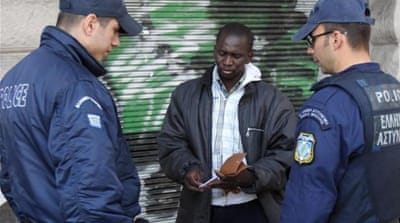 Greek Police officers check the IDs of migrants living in Athens [EPA]