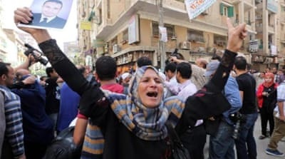 Relatives react outside a court in Minya, during the trial of supporters of ousted President Mohamed Morsi [EPA]