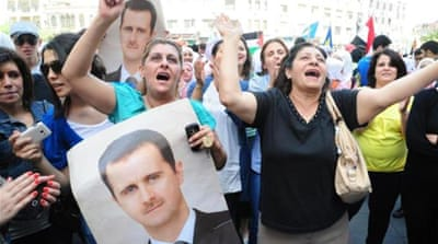 Syrian demonstrators shout slogans and wave portraits of Syrian President Bashar al-Assad in support of the president in Damascus on April 28 [AFP]