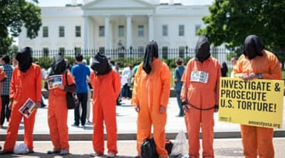 Protesters hold signs as they call for the closing of the Guantanamo Bay detention facility in front of the White House in Washington DC [AFP]