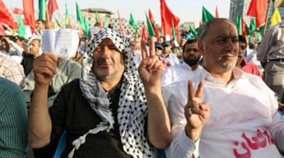 Iranians flash the sign of victory during a protest against ISIL's offensive in Iraq on June 24 in Tehran [AFP]