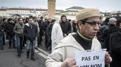 A Muslim man holds a placard, reading 'Not in my name' in eastern France [AFP]