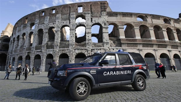 An alleged member of  the 'Ndrangheta crime syndicate is escorted by Italian Carabinieri police officers [AP]