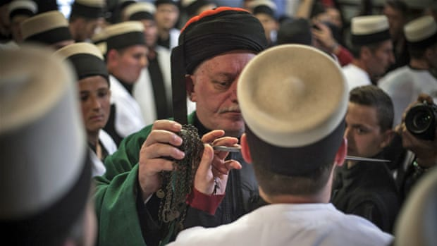 A member of the Bektashi Rufai sect piercing himself with a zarf during the Nowruz ritual [Ferdi Limani/Al Jazeera]