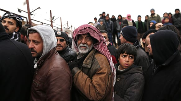 Syrian refugees wait for food near a refugee camp in Bab Al-Salama city, in northern Syria, on February 6 [Sedat Suna/EPA]