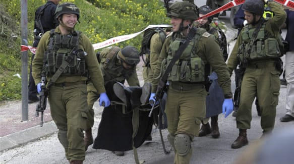 Israeli soldiers carry the body of one of two Palestinians killed after the stabbing attack in Hebron [AP]