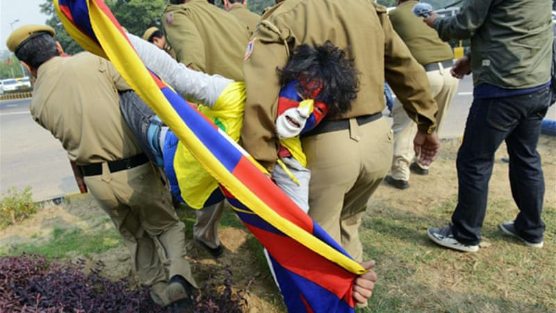 An activist waves the Tibetan flag as he is arrested by Indian police outside the Chinese embassy in New Delhi [AFP]