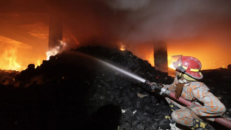 A Bangladeshi fireman examines burnt materials after the fire in the Tazreen Fashion plant in Savar in Dhaka [AFP]