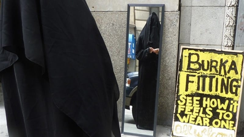 "A woman dons a burka as part of the ""Burka Fittings Across America"" project in New York City [Marie Rim/Al Jazeera]"