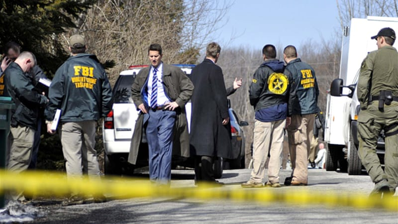 Federal agents stand outside the residence of TJ Lane, who allegedly shot one girl and four boys [Reuters]