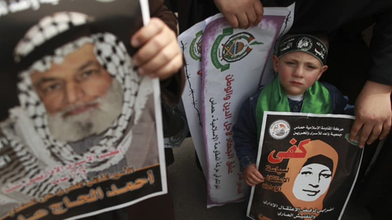 A Palestinian boy holds a poster depicting Hana Shalabi during a Gaza City rally [Reuters]