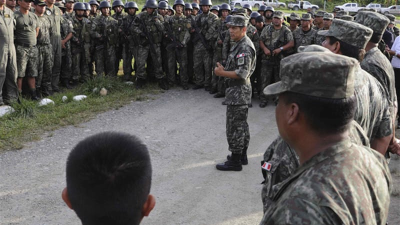 The father of Captain Nancy Flores, killed in a firefight with Shining Path rebels, kisses her pilot's helmet during her funeral in April [Reuters]