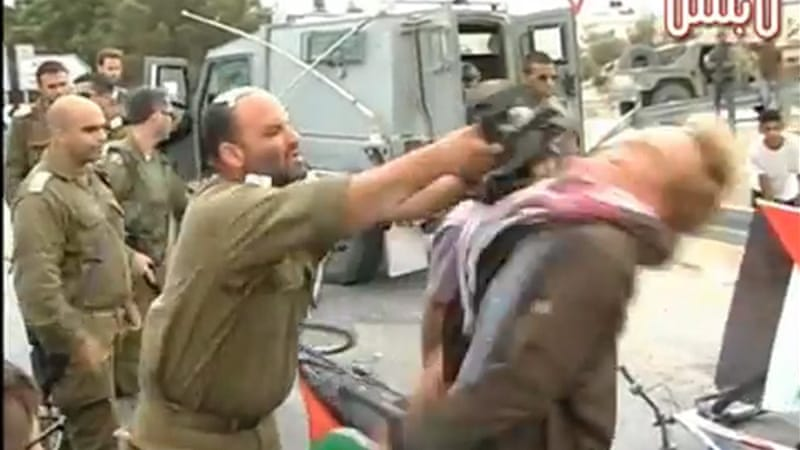 An Israeli soldier is seen hitting an activist in footage posted on YouTube