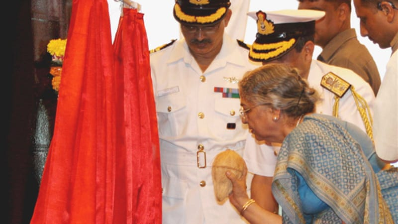 The Indian PM's wife breaks a coconut at the launch of India's first nuclear submarine, the INS Arihant, in 2009 [EPA]
