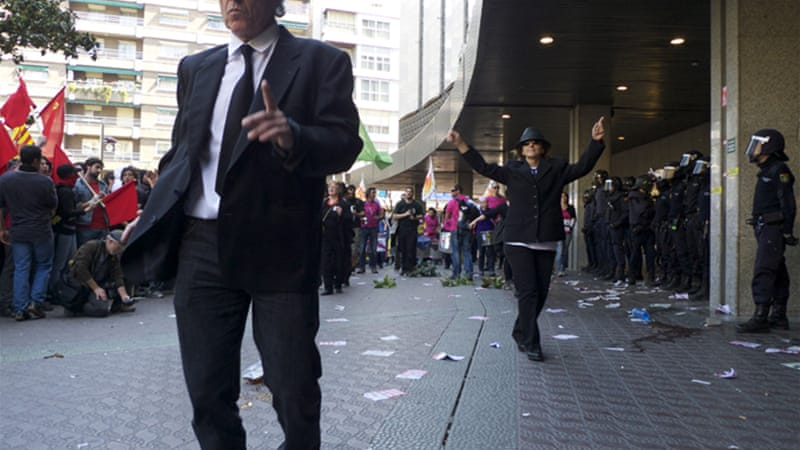 Protesters dressed up as bankers under police watch in Zaragoza, during the March 29 Spanish general strike [Al Jazeera/Pepe Escobar]