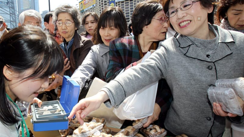 Women buy shiitake mushrooms produced in Iwaki city to help sell farm products [AP]