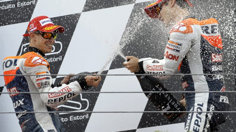 Stoner (L) celebrates victory with Honda teammate Dani Pedrosa, who finished third, in Estoril [AFP]