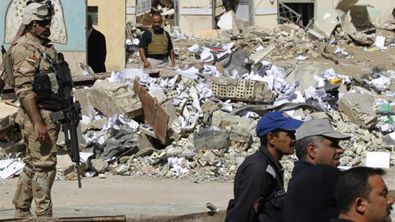 Iraqi security personnel inspect the site of an earlier car bomb attack in Baghdad on June 4 [Reuters]