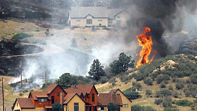 Smoke and flames encroach upon homes on the eastern front of the High Park fire near Laporte, Colorado  [Reuters]