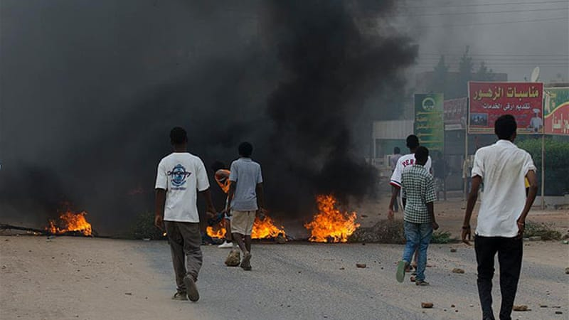 Smoke hung over Khartoum and tear gas stung the air on Friday as police tried to  disperse protests [Al Jazeera]