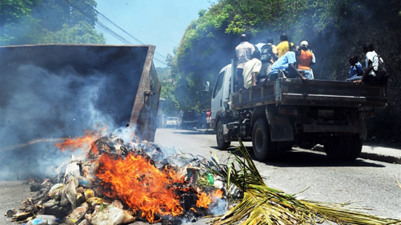 Police fired tear gas in an attempt to control the protesters in Port-au-Prince, some of whom threw rocks [AFP]
