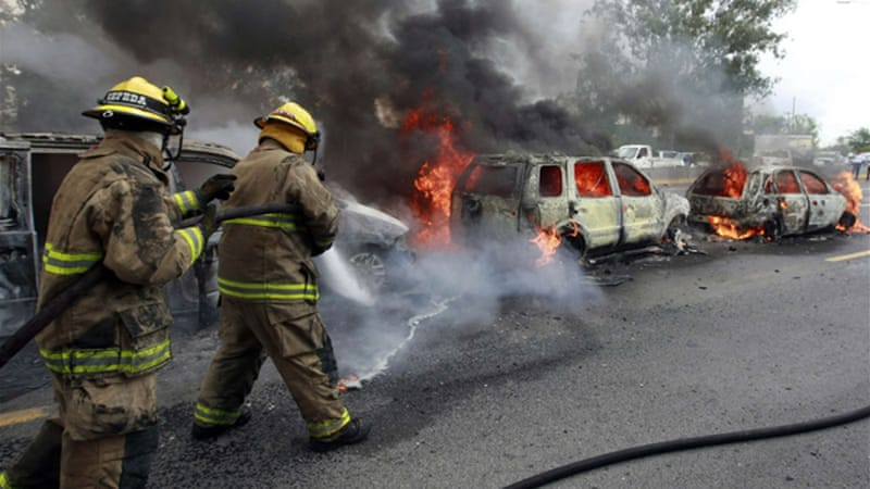 Firefighters were deployed to extinguish lines of smoldering vehicles in Mexico's second largest city [Reuters]