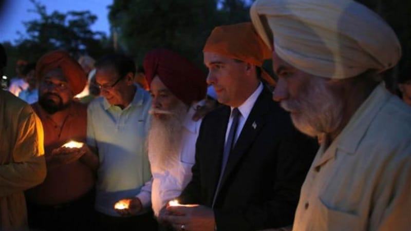 Wisconsin Governor Scott Walker along with members of the Sikh community attends a candle light vigil at the Sikh Religious Society of Wisconsin for the victims of the shooting at the Sikh Temple of Wisconsin [Getty Images]