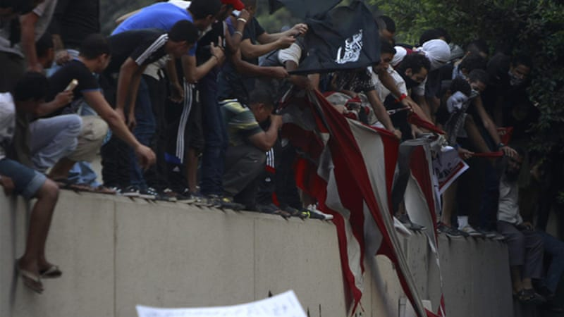 Security forces dispersed protesters who tore up an American flag pulled down from the US embassy in Cairo [Reuters]