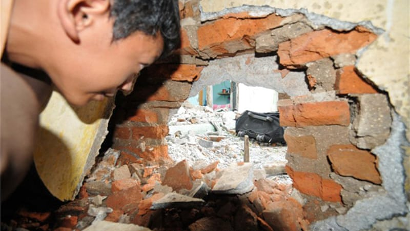 A boy peers at a hole after a bomb squad defused homemade bombs they found in the house of suspects in Solo [AFP]